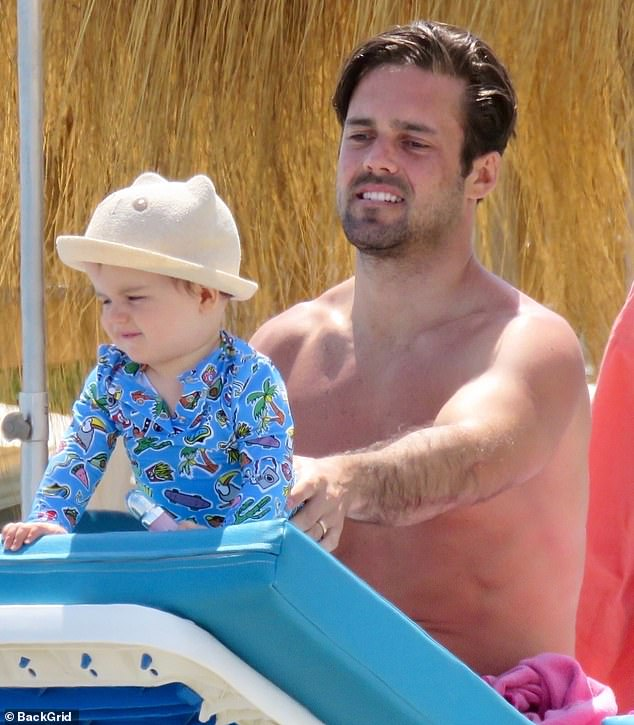 Doting dad: Former Made In Chelsea star Spencer rocked pink swimming shorts, sweeping his raven locks back after a dip in the sea