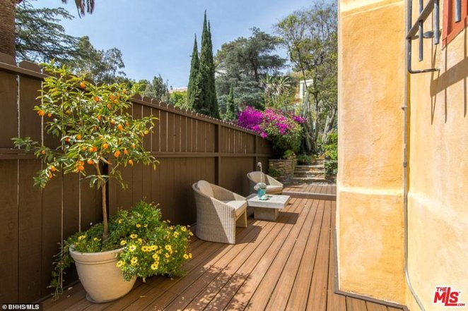 Outdoor seating: These comfortable-looking wicker chairs have been placed next to a garden fence outside the property, with the colors and plant life of the garden in full bloom