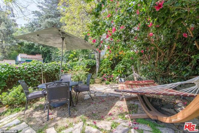 Garden: There are several options for outdoor seating on sunny days here, with four chairs laid out around a table underneath a large umbrella and a hammock stretched out on a curved piece of wood on the right