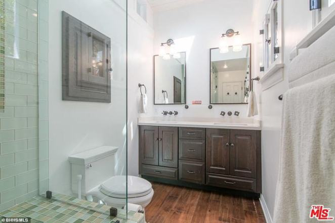 Another bathroom: This one includes a toilet next to another glass-fronted shower, with wood-paneled drawers and cabinets underneath the sinks and two large mirrors on one of the walls