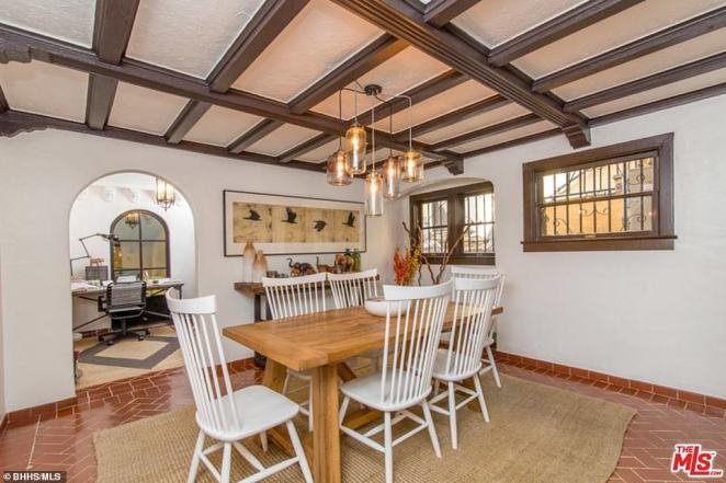 Dining room: A wooden table is laid out with six chairs for the property's new owners to eat at. Real estate agents Berkshire Hathaway say the 'charming' study adjacent to this room also overlooks the living room