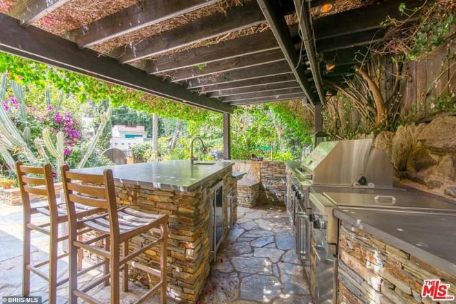 Outdoor kitchen: The home in California features these open-air cooking facilities, covered by a roof and decorated with brickwork, with a view over the colorful plants and flowers in the garden