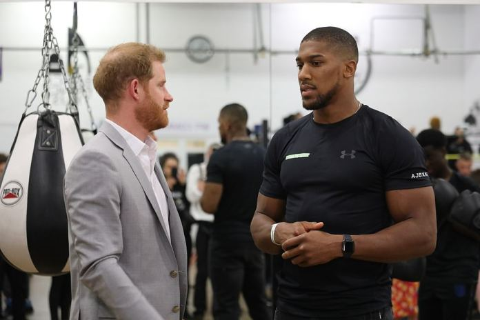 Prince Harry was greeted by Anthony Joshua, before being introduced to young people taking part in the boxing training session