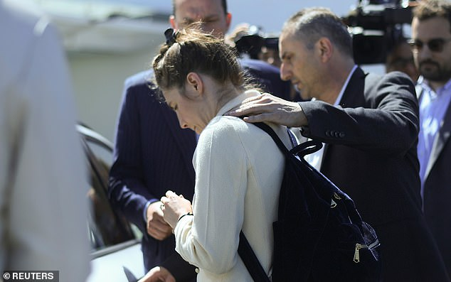 The writer and activist shied away from the cameras when she landed in Milan and bowed her head as she left the airport