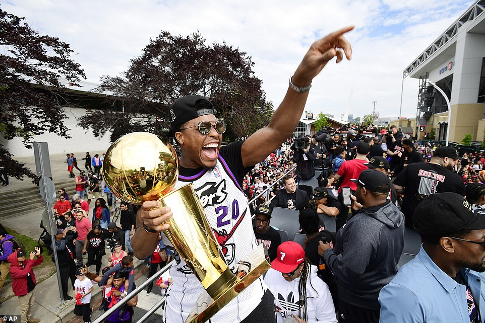 Toronto Raptors guard Kyle Lowry, the team's longest-tenured player, enjoys Monday's parade with the Larry O'Brien trophy