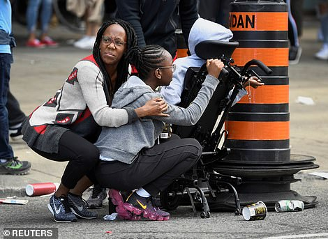 People take cover after reports of shots fired in the area where crowds gathered in Nathan Phillips Square to celebrate the Toronto Raptors NBA title