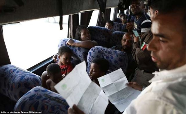An official  (right) revises the documents of migrant passengers (pictured) on a bus in southern Mexican state of Chiapas