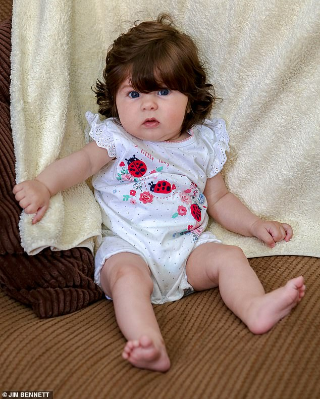 Five-month-old Dolly Canham, pictured, from Bromley, south east London, was born with 'incredibly thick hair' and it is now almost shoulder length