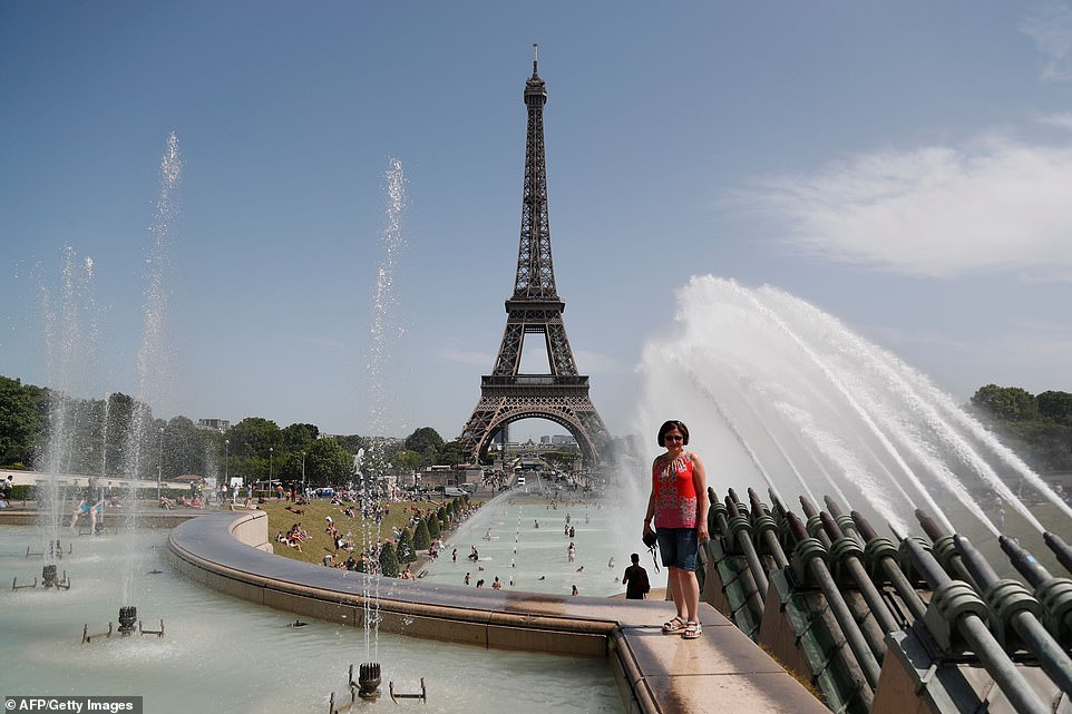 A woman poses as people bathe in theTrocadero Fountain near the Eiffel Tower as the temperature climbed over the course of the day