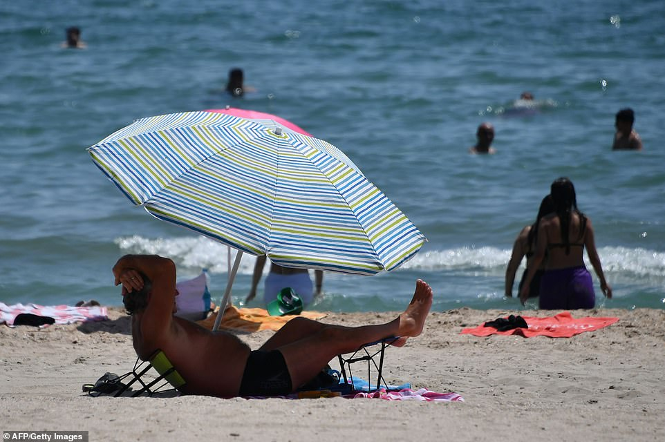With France, Spain, Italy and parts of central Europe particularly badly hit by the high temperatures, officials urged people to take common sense precautions - complaining that this was not always the case. Pictured: A man protects himself from the sun under an umbrella during a heat wave in Palavas-les-Flots, southern France