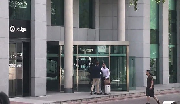 The lawyer was carrying a suitcase, and shook hands with two men before heading inside