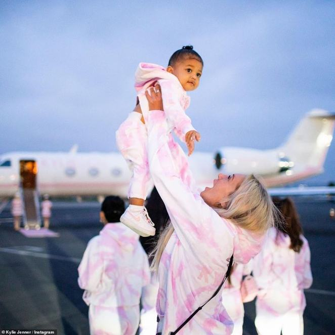 Joy: One of Kylie's beloved pals held up her daughter Stormi before she boarded the plane with a smile