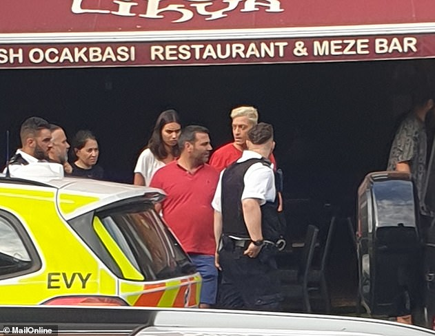 Mesut Oszil (dyed blonde hair with his wife Amine next to him) can be seen talking to officers outside a Turkish restaurant they dived into to escape