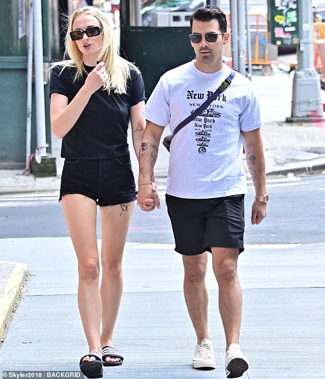 Summer cool:Sophie, 23, paired it with Adidas Slide sandals, a gold chain link necklace and square black sunglasses. While the Sucker singer, 29, wore a white tee with 'New York' written in different fonts, black shorts and white sneakers
