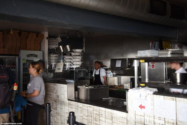 A chef in Cornwall stands in the dark as machines and lights were switched off during the mass outage this evening. It has impacted the Fistral Beach Boardmasters surf competition