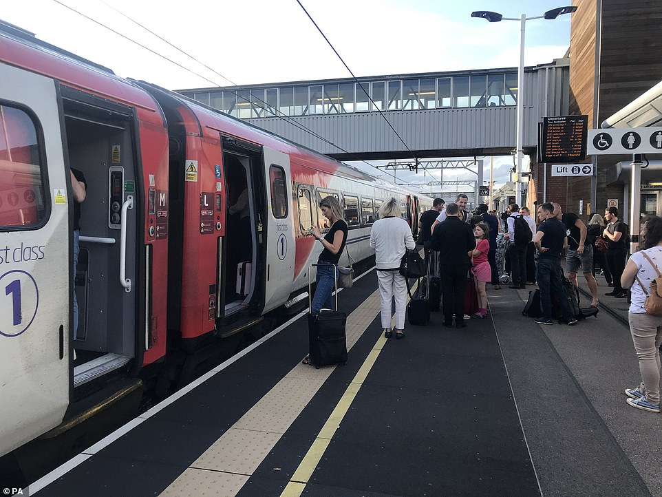 Passengers wait for news at Peterborough station during travel disruption on the East Coast mainline, after a large power cut has caused