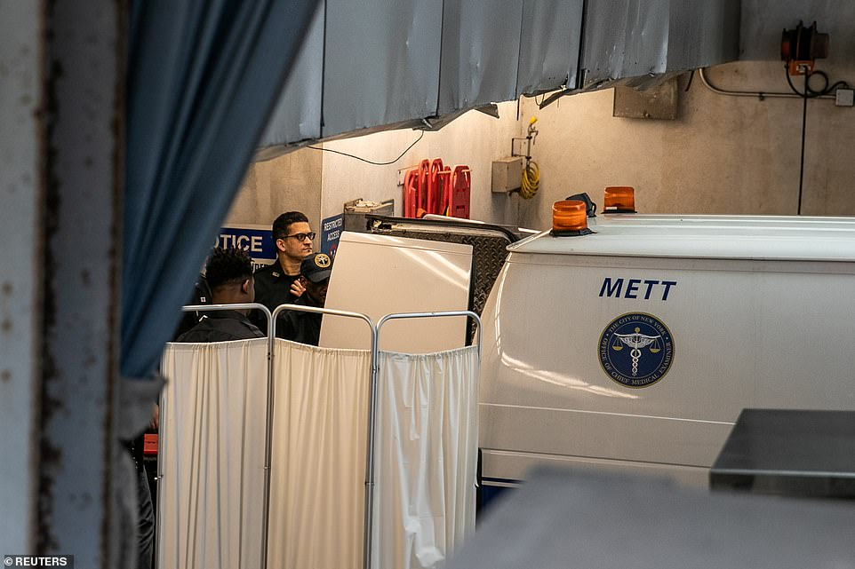 Hospital staff are seen preparing a white coroner's van before Epstein's body was loaded inside
