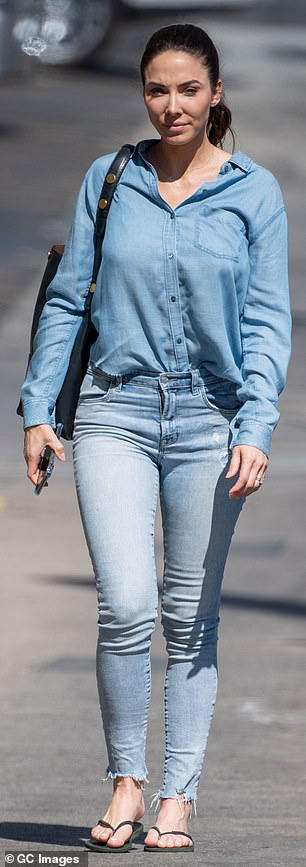 No fuss: She paired her top with a pair of acid wash jeans with frayed hems and plain black flip flops