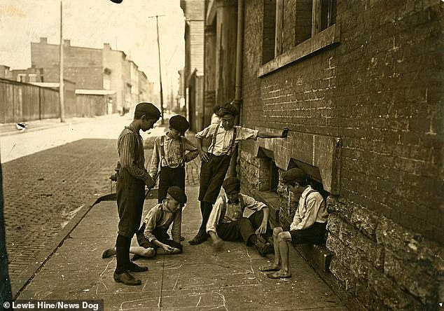 Six boys are pictured playing a game of Craps on a street in Cincinatti, Ohio in August 1908. The boys, who can be no older than 10, are dressed in ragged clothes and some are without shoes. By 1910, there were two million children in the American workforce
