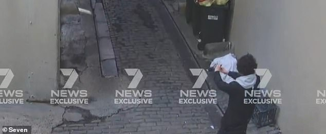 New footage has emerged of Ney wandering into an alley moments after he allegedly killed Ms Dunn just before 2pm, pausing and then appearing to hold a phone in front of his face (pictured)