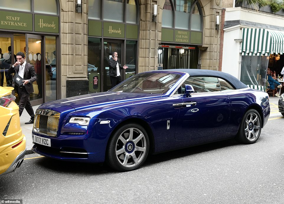 A stunning blue Rolls-Royce Dawn worth£280,000 is parked outside the private car park entrance to Harrods