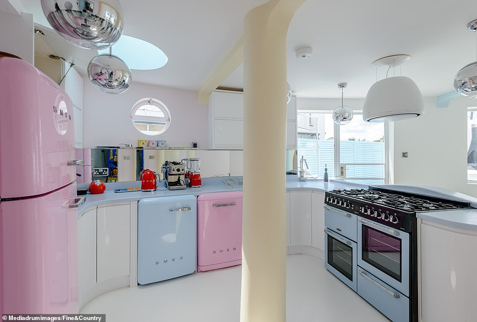 The one-of-a-kind masterpiece combines retro and modern styles typical of the period with pastel pinks and blues complementing the unusual curves in the kitchen