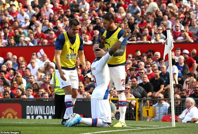 Ayew is congratulated by Palace substitutes Scott Dann and Connor Wickham after managing to score