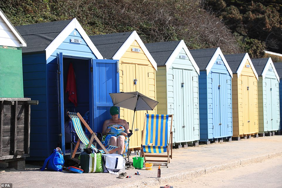 A woman sits alone reading under the shade of an umbrella outside a beach hut in Bournemouth.It is expected to get even hotter tomorrow, with temperatures potentially soaring higher on an August 26 than they've ever been since records began