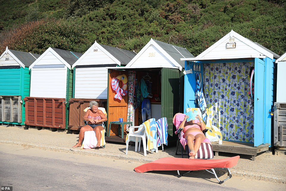 Many of the beach huts had been opened up today as bathers caught a tan while sitting out in the sun in Bournemouth today