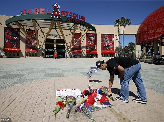 Los Angeles Angels fan Pete Soto adds to a make- shift memorial at Angels Stadium in Anaheim for pitcher Tyler Skaggs at Angel Stadium