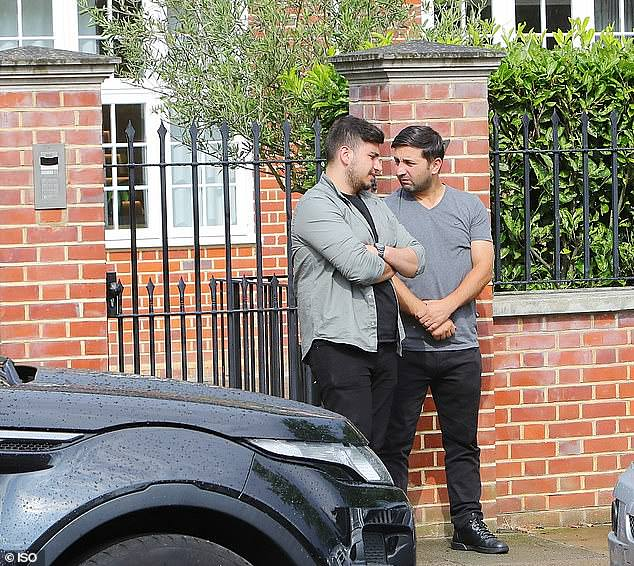 Security staff, who are not involved in the case, are pictured outside Ozil's home in north London, in July