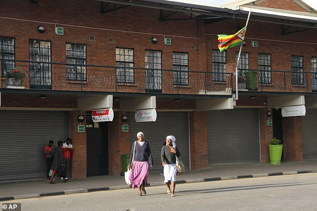 The Zimbabwean flag flies at half-mast on a street in Harare, Saturday