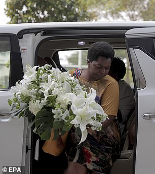 A woman carrying a wreath arrives at the Singapore Casket building