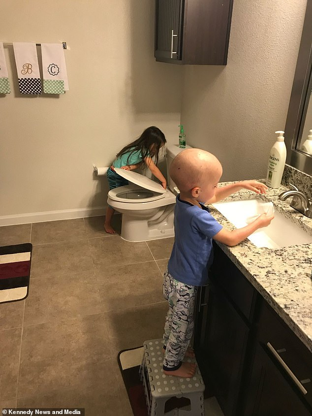 In difficult times: Aubrey cleans up for her younger brother after months of unwell hospital chemotherapy