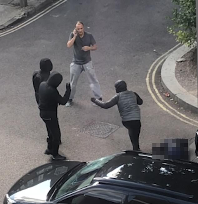 During the video a masked man shouts: 'He's shot himself' before he and two others run off