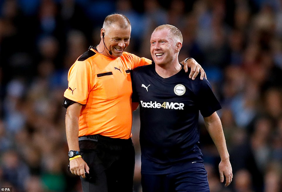Red Devils legend Paul Scholes (right) has a laugh with referee Mark Halsey (left) during Kompany's testimonial