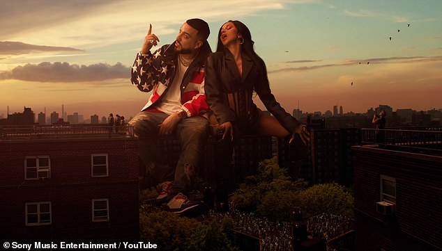 Hanging out:Cardi begins her verse sitting on top of a building next to French Montana (real name (Karim Kharbouch), wearing a black suit coat, gold hoop earrings and black knee-high boots