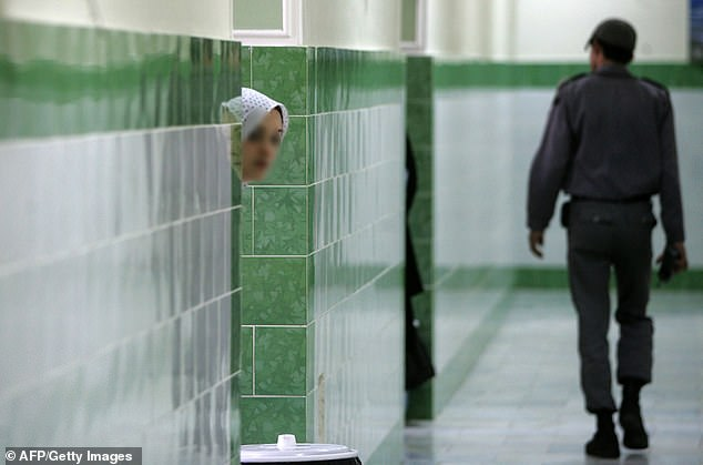 An Iranian inmate peers from behind a wall as a guard walks by at the female section of the infamous Evin jail, north of Tehran