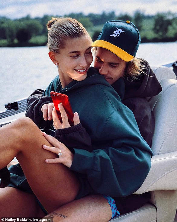 Bling bling: Baldwin showed off her massive engagement ring while cuddling Justin