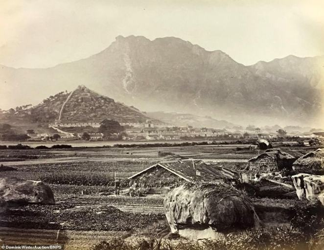 A rural scene across modern-day Kowloon, today the most populated urban area in Hong Kong, then a sparsely-populated rural landscape with farming huts dotted across the fields