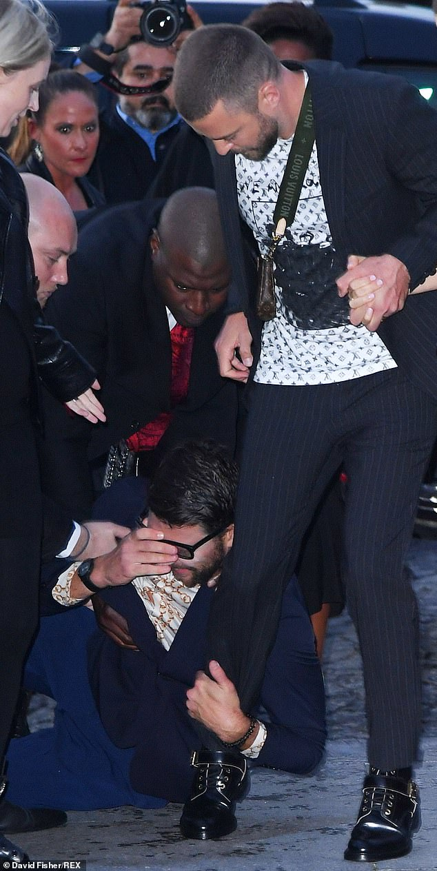 Let go! The unknown man held onto the superstar's leg as he attempted to walk into the show
