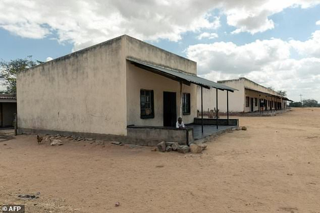 A child stands outside a general store which serves beneficiaries of a World Food Programme  sponsored cash transfer assistance programme