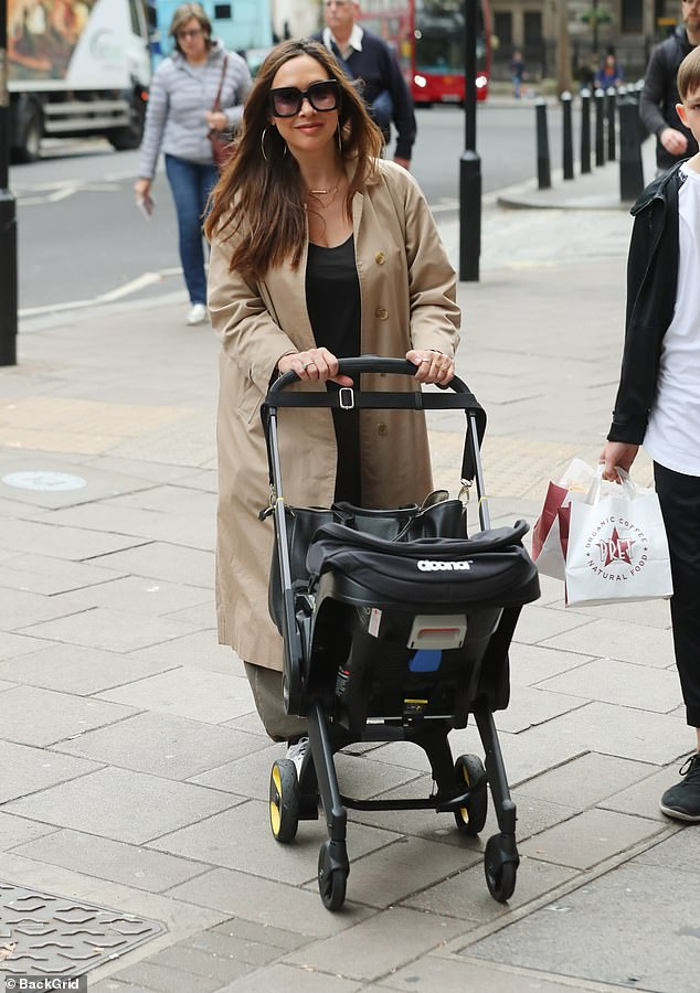 All wrapped up:Her long beige mac added an extra layer of warmth as she trotted along pushing her youngest child's buggy