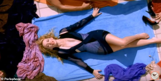 Blast from the past!In the original clip, sings and writhes around on a towel while shirtless dancers surround her (pictured)