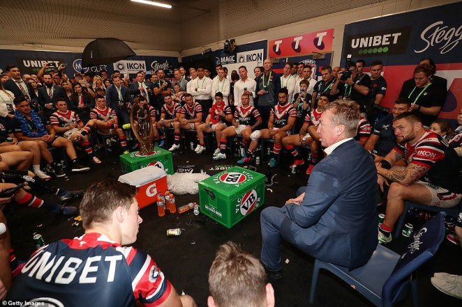 Head coach of the Roosters Trent Robinson talks to players in the changing room following the Roosters victory