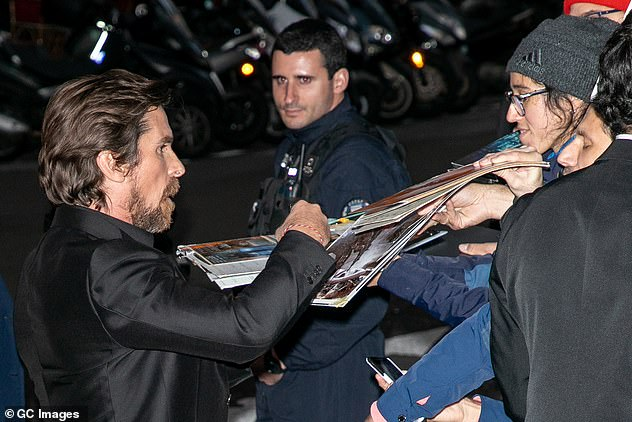 Fans: Christian took some time to sign autographs outside the venue on Sunday night