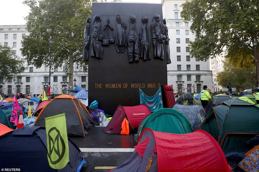 Protesters lean their banners, tents and event a lilo against the memorial for all the women who served our country in the Second World War