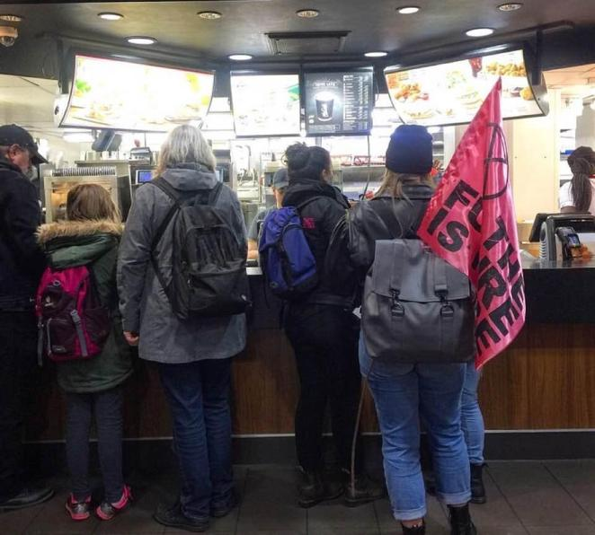 While Animal Rebellion activists demanded the meat market is turned into a 'plant-based emporium' their fellow protestors queued up for snacks at McDonald's (pictured)