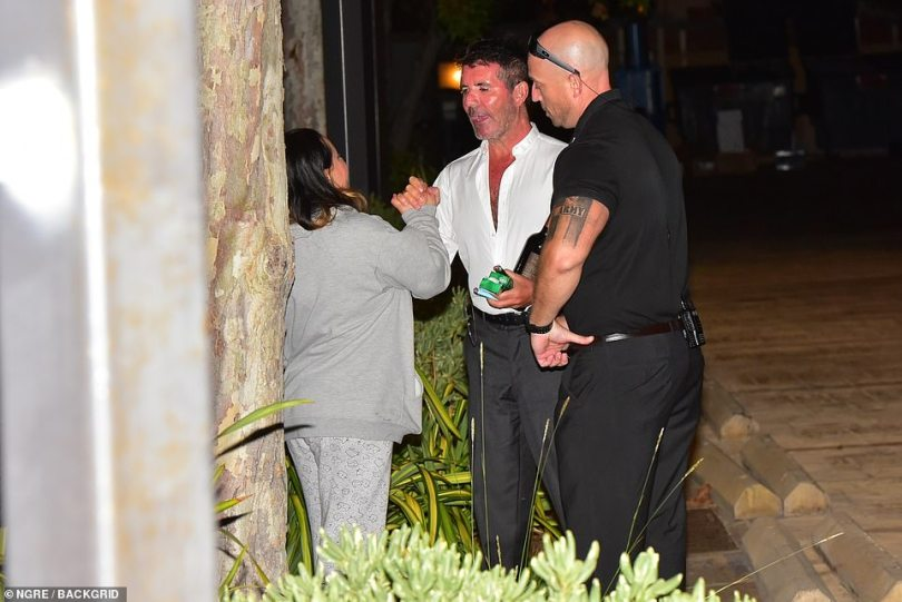 Popular: Simon was seen greeting a fan while his security stood close by during his long walkabout outside the restaurant