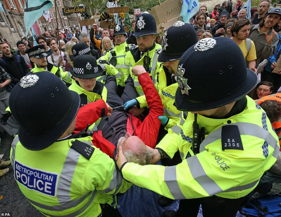 It took eight police officers to remove a single protester on Millbank today as the Met pledged to arrest anyone who has not yet removed